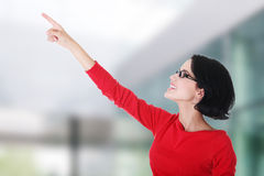 Excited young woman pointing on copy space Stock Photo