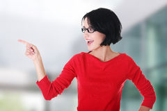 Excited young woman pointing on copy space Royalty Free Stock Images