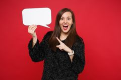 Excited young woman pointing index finger on empty blank Say cloud, speech bubble for promotional content isolated on. Red background. People sincere emotions royalty free stock photography