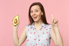 Excited young woman pointing index finger up with new idea, hold half of fresh ripe avocado fruit isolated on pink. Pastel background. People vivid lifestyle stock image