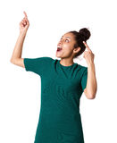 Excited young woman pointing up and laughing Stock Photography