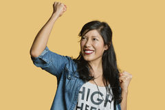 Excited young woman with raised fist while looking away over colored background Stock Photo