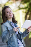 Excited young woman reading digital tablet outdoor Stock Photography