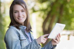 Excited young woman reading digital tablet outdoor Royalty Free Stock Photos