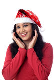 Excited young woman in Santa hat against white Stock Image