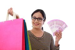Excited young woman with shopping bags and 2000 rupee notes royalty free stock image
