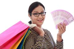 Excited young woman with shopping bags and 2000 rupee notes royalty free stock images