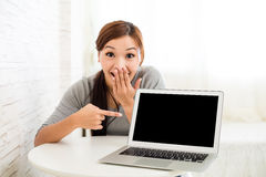 Excited young woman showing laptop computer. At home Royalty Free Stock Photo