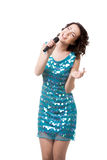 Excited young woman singing in short sparkling blue dress. Slender young female in short sparkling blue dress, having fun, singing with dedication, holding stock image