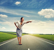 Excited young woman standing on the road. And pointing at something Stock Images