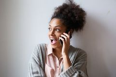 Excited young woman talking on mobile phone Stock Photo