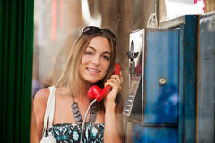 Excited young woman in telephone box outdoor. Excited young woman making a phone call in telephone box Royalty Free Stock Images