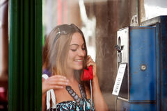 Excited young woman in telephone box outdoor. Excited young woman making a phone call in telephone box Stock Images