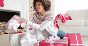 Excited young woman unwrapping her Christmas gifts stock footage