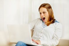 Excited young woman using a laptop Stock Photos