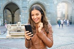 Excited young woman using smart phone outdoors.  Stock Image