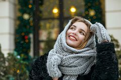 Excited young woman wearing grey scarf enjoying winter holidays. Space for text. Excited brunette woman wearing grey scarf enjoying winter holidays. Empty space royalty free stock photo