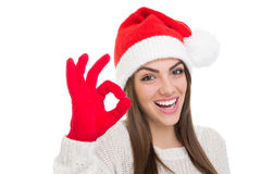 Excited young woman wearing Santa Claus hat gesturing ok Stock Images