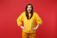 Excited young woman in yellow fur sweater with opened mouth standing with arms akimbo isolated on bright red wall. Background in studio. People sincere emotions stock photo