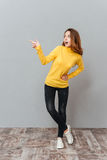 Excited young woman in yellow sweater standing and pointing away. Cheerful excited young woman in yellow sweater standing and pointing away over gray background Stock Image