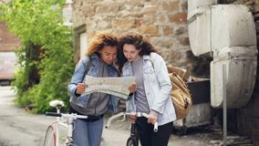 Excited young women bike travellers are looking at map and laughing looking around while standing with bicycles in the. Excited young women modern bike stock video footage