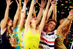 Excitement. Photo of excited teenagers raising their arms in joy royalty free stock image