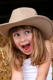 Excitement. A cute young girl in a cowgirl hat sitting on haybales in a barn stock photos