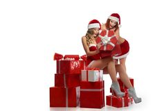 Two sexy Christmas girls posing with a pile of presents. Excitement all around. Horizontal full length of two gorgeous sexy female models wearing Christmas Royalty Free Stock Photos