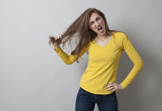 Excitement and pain concept for angry 20s girl. Excitement and pain concept - angry 20s girl standing in plugging her hair out for pain and frustration,studio Stock Photography