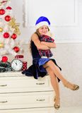 Excitement replaced with strong feeling satisfaction. Little girl santa hat satisfied christmas gift. Happy new year. Concept. Kid sit near christmas tree hold royalty free stock image