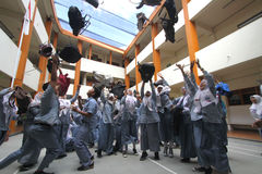 Excitement school graduation exam. Students carried away emotion during the announcement of the results of final exam school in Solo, Central Java, Indonesia stock photography