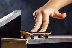 An exciting activity for a child, riding a mini skateboard or fingerboard on a specially equipped track. Closeup royalty free stock photography