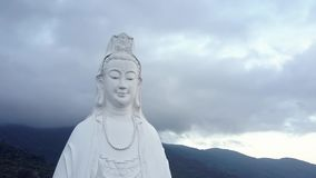 Aerial view white buddha statue with necklace against hills. Exciting aerial close view white buddha statue with necklace against hills under grey cloudy sky in stock footage