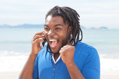 Exciting african american guy with dreadlocks at phone Stock Images