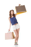 Exciting Asian shopping woman holding bags. Full length portrait isolated on white Royalty Free Stock Photos