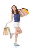 Exciting Asian shopping woman holding bags. Full length portrait isolated on white Royalty Free Stock Photo