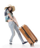 Exciting Asian woman drag a luggage. Full length portrait isolated on white background Royalty Free Stock Photos