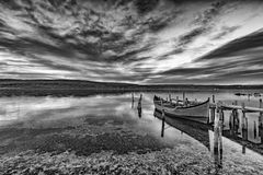 Exciting black and white. Landscape on a lake with wooden pier and boat Royalty Free Stock Photo