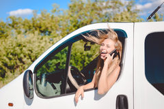 Exciting Blond Female At The Wheel Speaking By Stock Image
