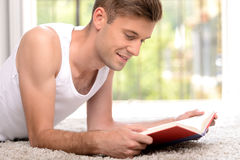 Exciting book.  Side view of handsome young men reading a book w. Exciting book.  Side view of handsome young man reading a book while lying on the floor Stock Photography