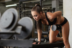 Exciting brunette exercising with dumbbells in gym. Image of exciting brunette exercising with dumbbells in gym Stock Photography