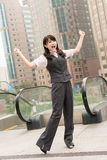 Exciting business woman. Raised hand in outside of city Royalty Free Stock Image