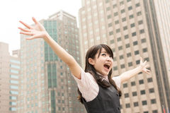 Exciting business woman. Raised hand in outside of city Royalty Free Stock Photo
