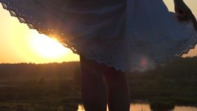Young Woman Frolics With The Hem of Her White Folk Dress at Sunset in Slo-Mo stock footage