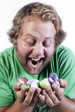 Exciting Easter. Caucasian young man holding handful of colourful easter egg candy Royalty Free Stock Photography