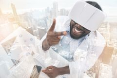 Pleased African American doctor wearing virtual glasses. Exciting emotions. Young pleased African American doctor putting forward two fingers while looking at Royalty Free Stock Photo
