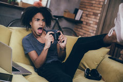 Exciting game!. Excited young African man playing video game and keeping his mouth open while sitting on the couch at home Stock Photography