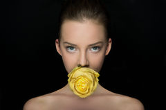 Exciting girl's portrait with yellow rose. The girl, looking in the picture area, with bright eyes and yellow rose in her lips poses in studio on black Stock Image