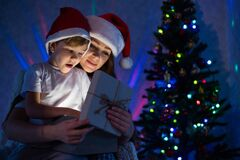 Exciting Mom and son open a glowing gift box at a magical Christmas night.