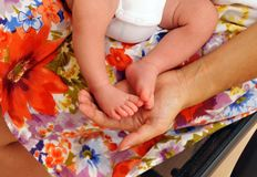 Exciting scene of a woman caressing the feet of her first baby with tenderness. Young woman with the small feet of her baby in the hands Royalty Free Stock Photography